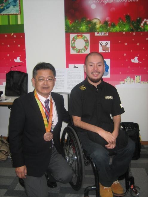 乗松選手と乗松選手のメダルをかけてもらっている希望荘館長の写真